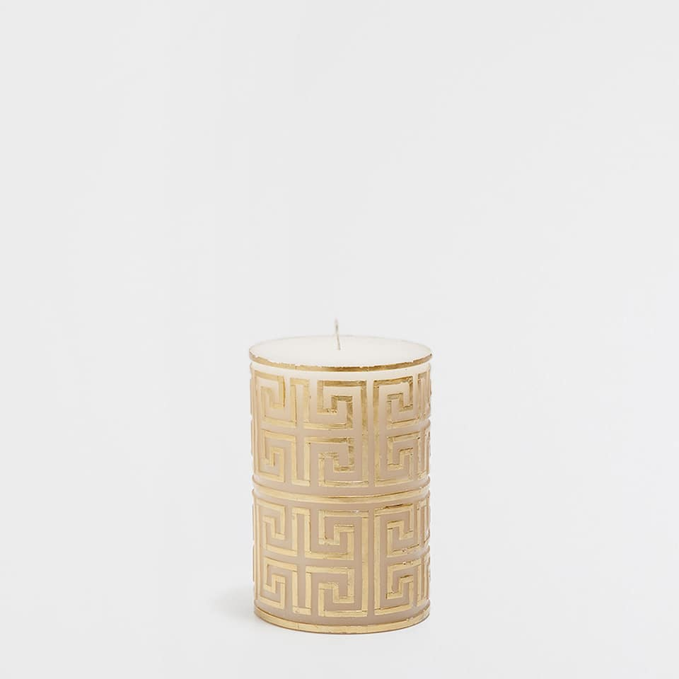 Golden raised-design cylindrical candle