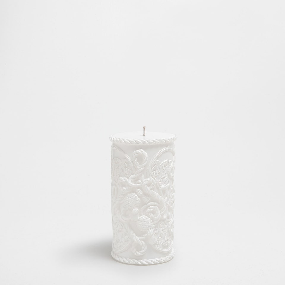 White raised-design cylindrical candle