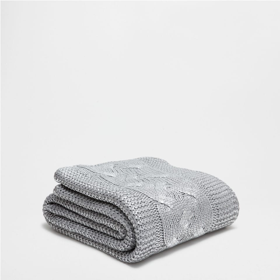 CABLE-KNIT BLANKET WITH A METALLIC OVERLAY