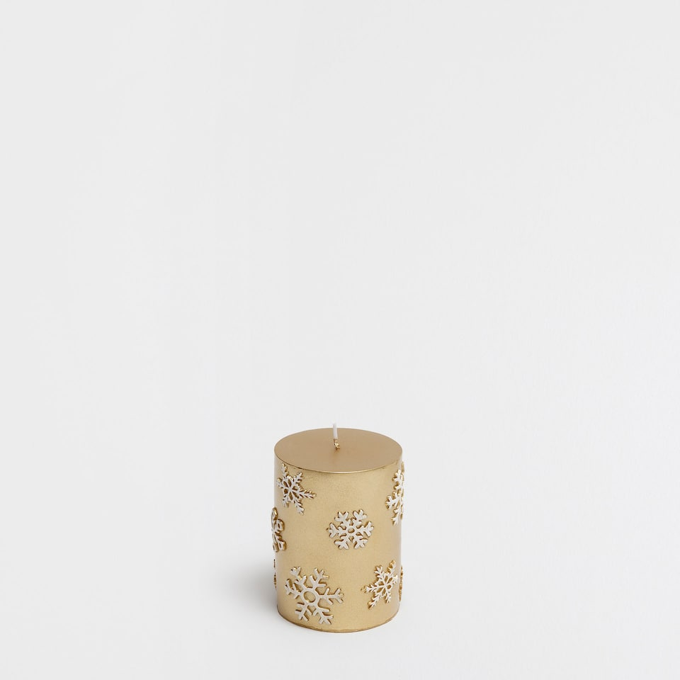 Golden candle with snowflakes
