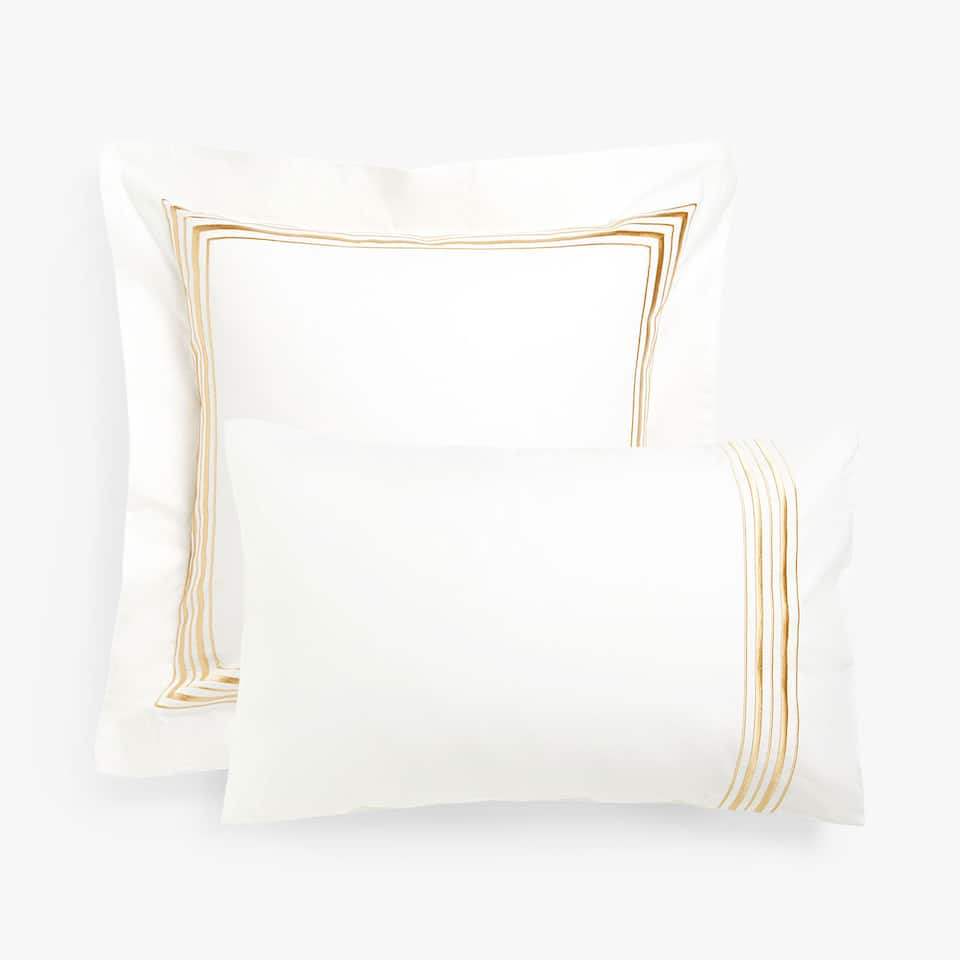 Pillow case with gold embroidered edge