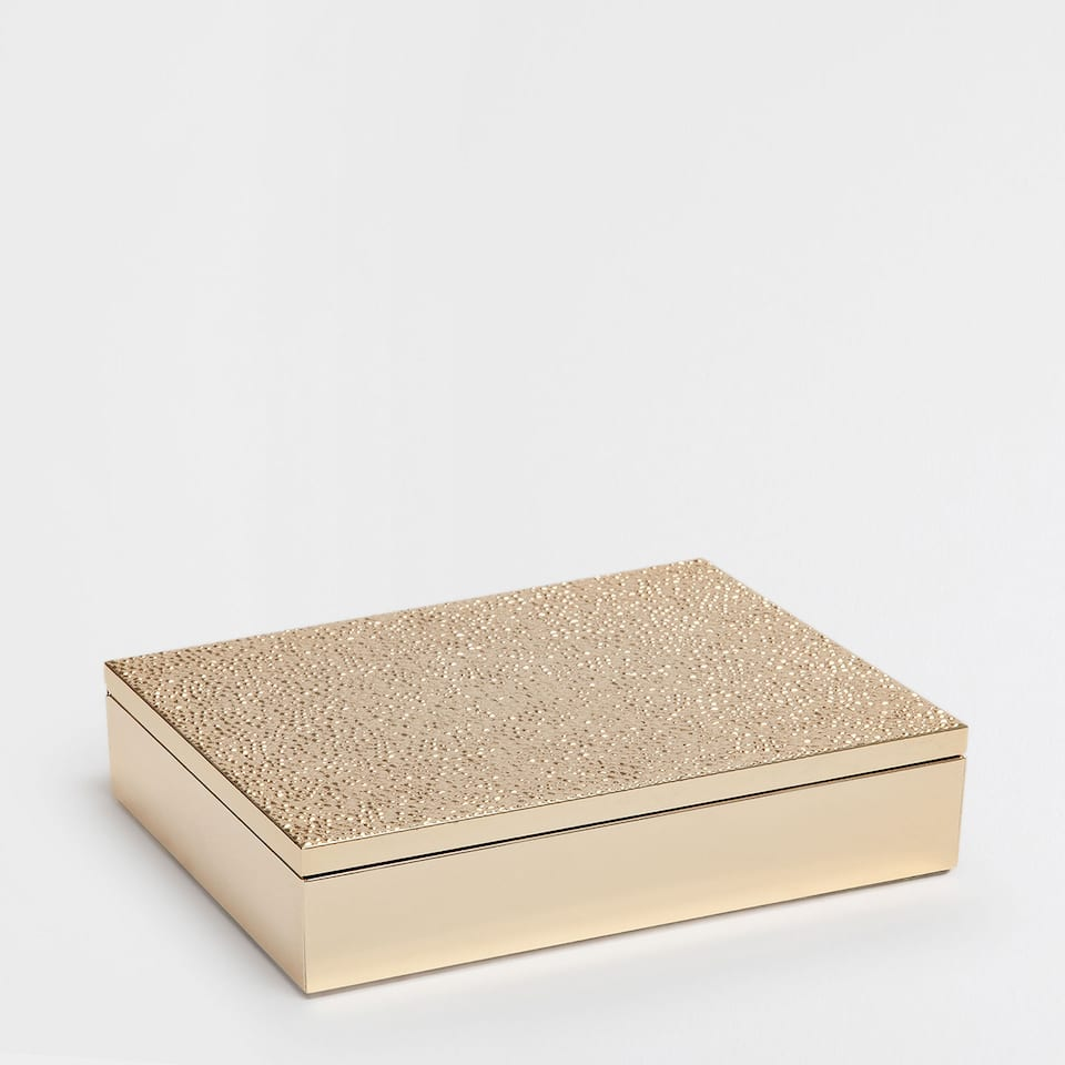 Golden metallic box with raised dots