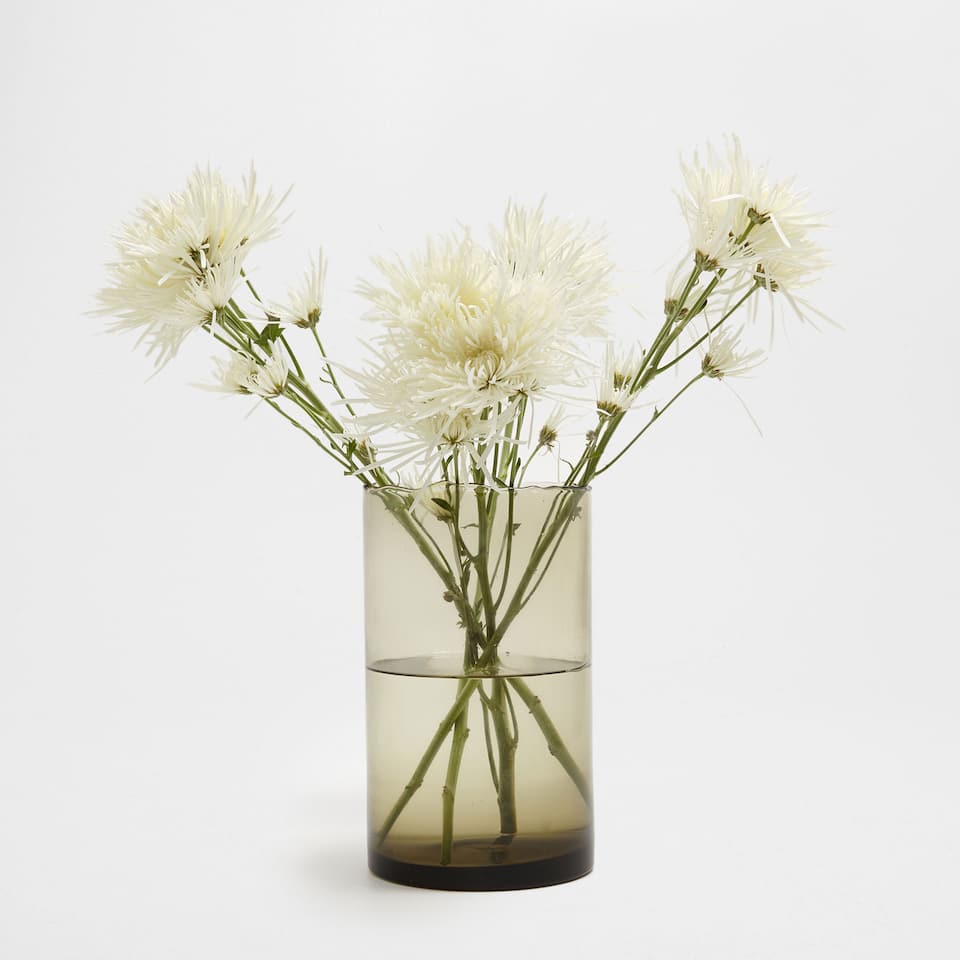 GREEN CYLINDRICAL GLASS VASE WITH AN IRREGULAR EDGE