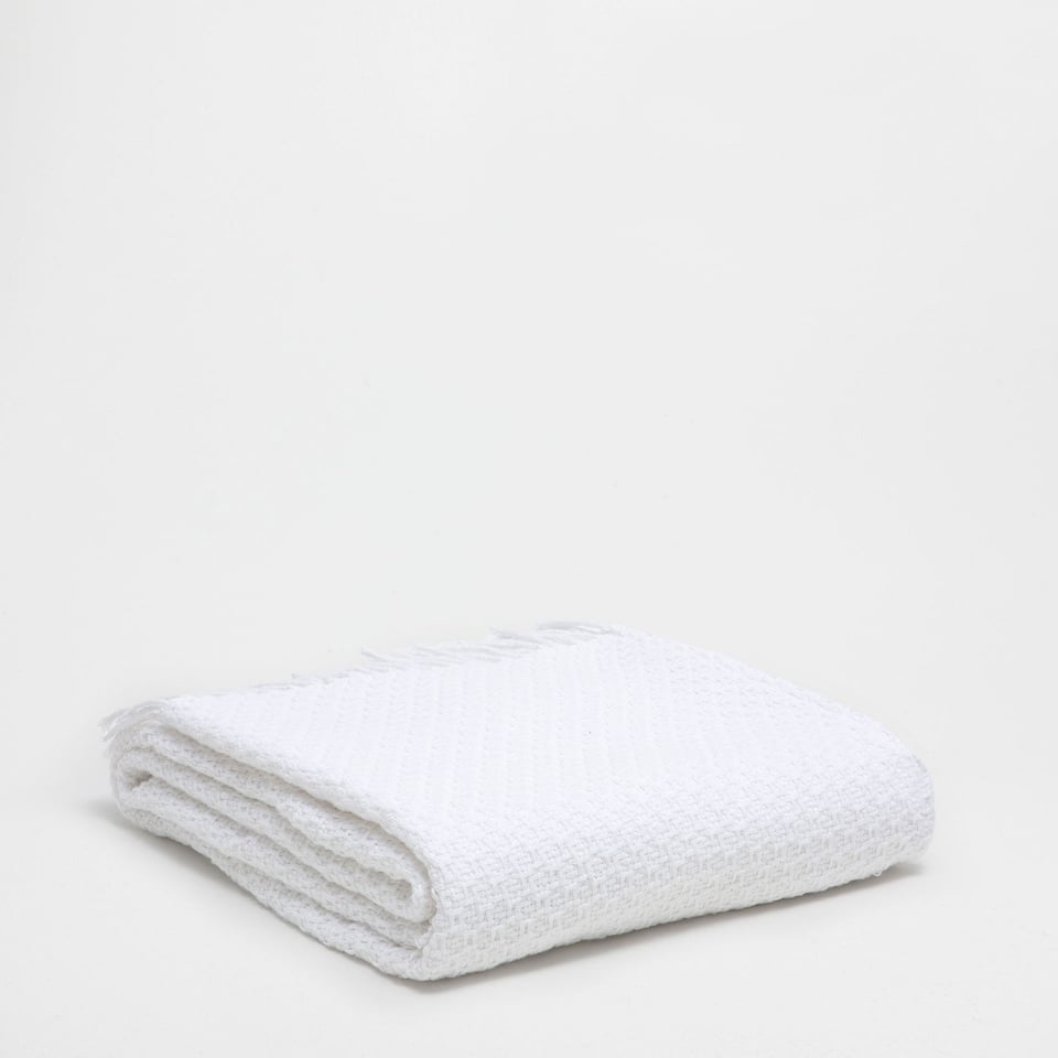 WHITE FABRIC BLANKET WITH A RAISED PATTERN