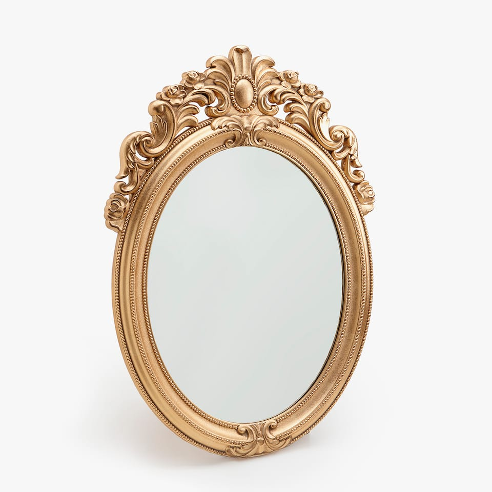 Oval mirror with detailing on the top
