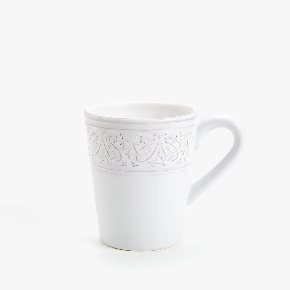 White raised design earthenware mug.
