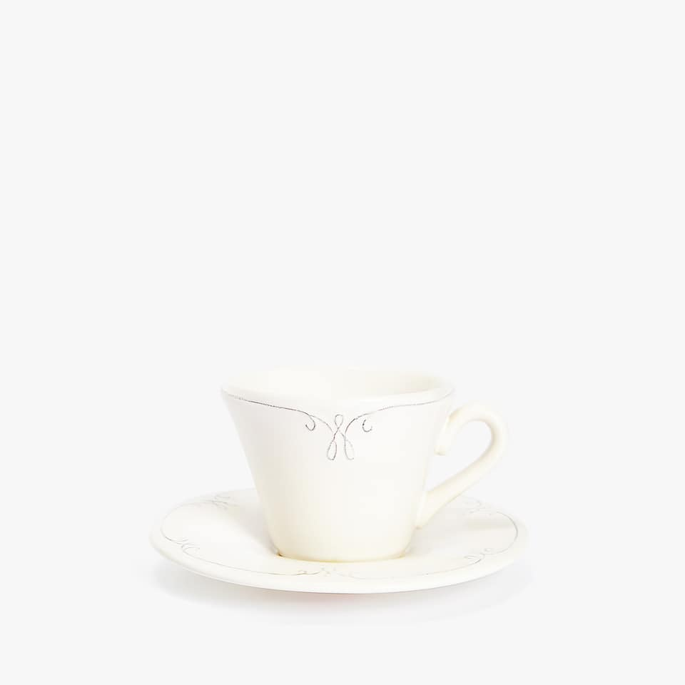 EARTHENWARE TEACUP AND SAUCER WITH RAISED-DESIGN RIM
