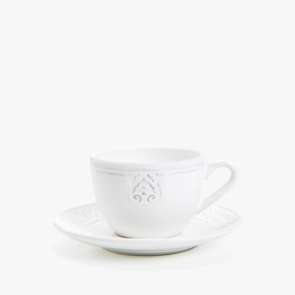 WHITE RAISED-DESIGN EARTHENWARE TEACUP AND SAUCER