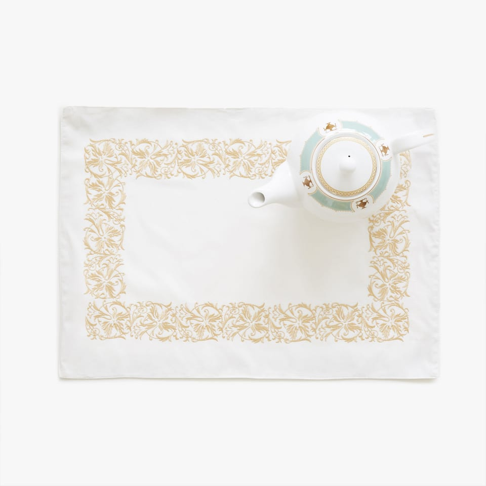 White placemat with gold embroidery
