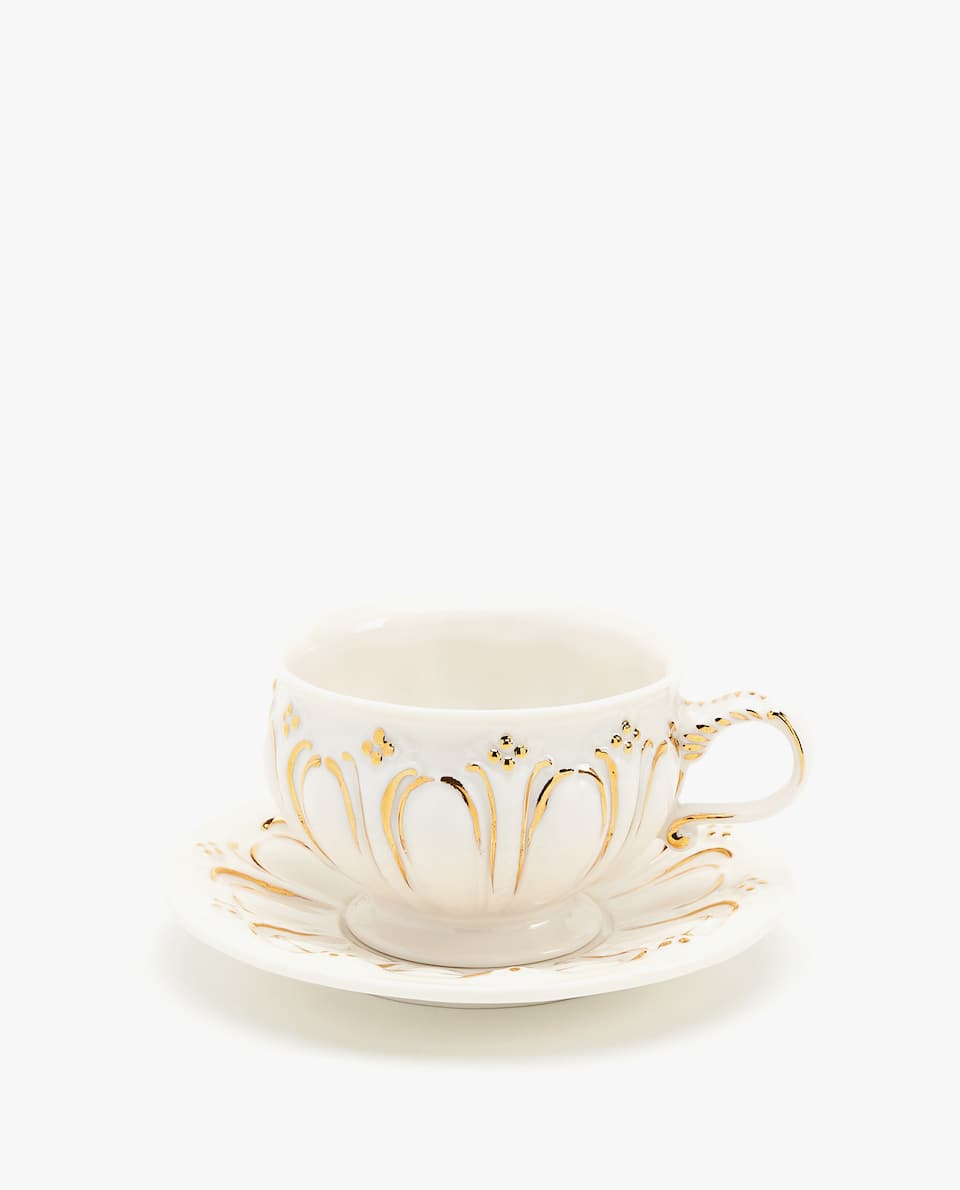 Scalloped porcelain teacup and saucer with gold motif