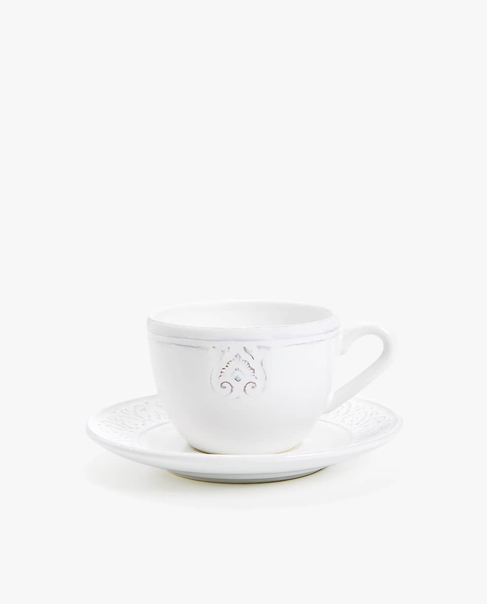 WHITE RAISED-DESIGN EARTHENWARE COFFEE CUP AND SAUCER