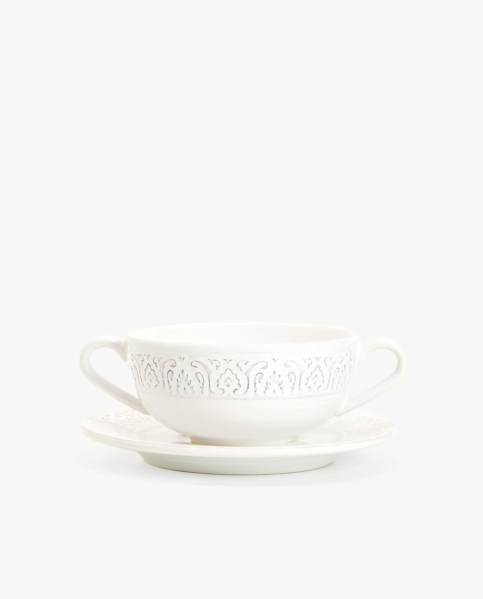 WHITE RAISED-DESIGN EARTHENWARE SOUP BOWL AND SAUCER