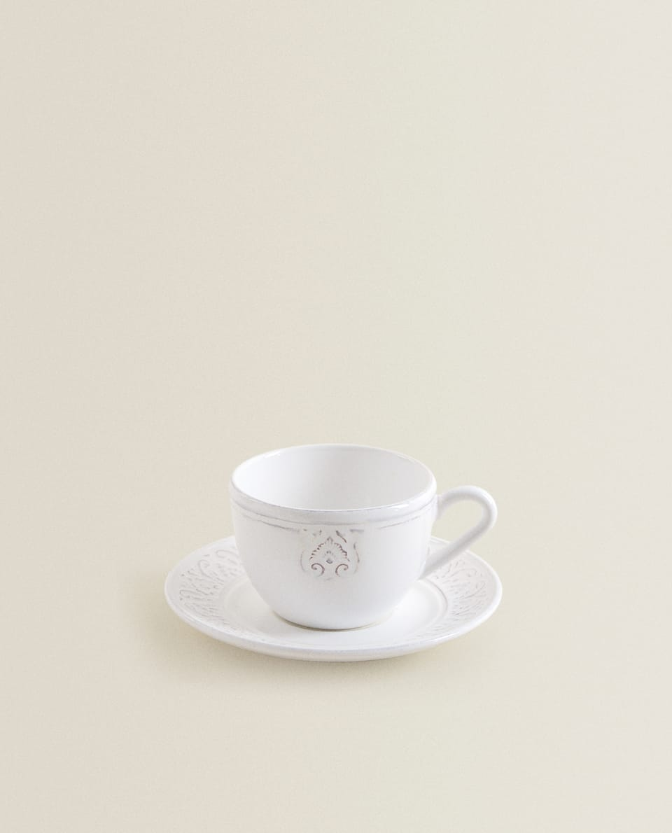 RAISED-DESIGN EARTHENWARE CUP AND SAUCER