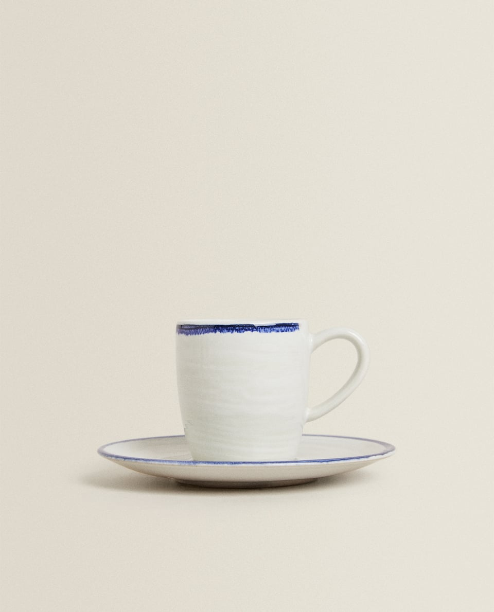 RAISED STONEWARE COFFEE CUP AND SAUCER WITH BLUE RIM
