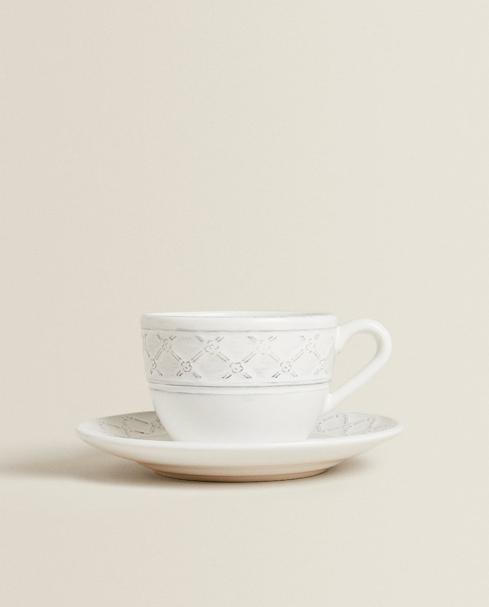 RAISED EARTHENWARE TEACUP AND SAUCER