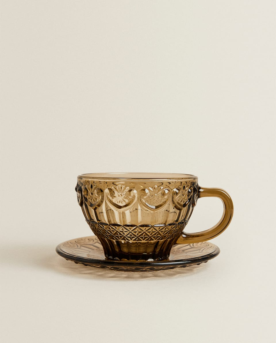 GLASS TEACUP AND SAUCER WITH RAISED DESIGN